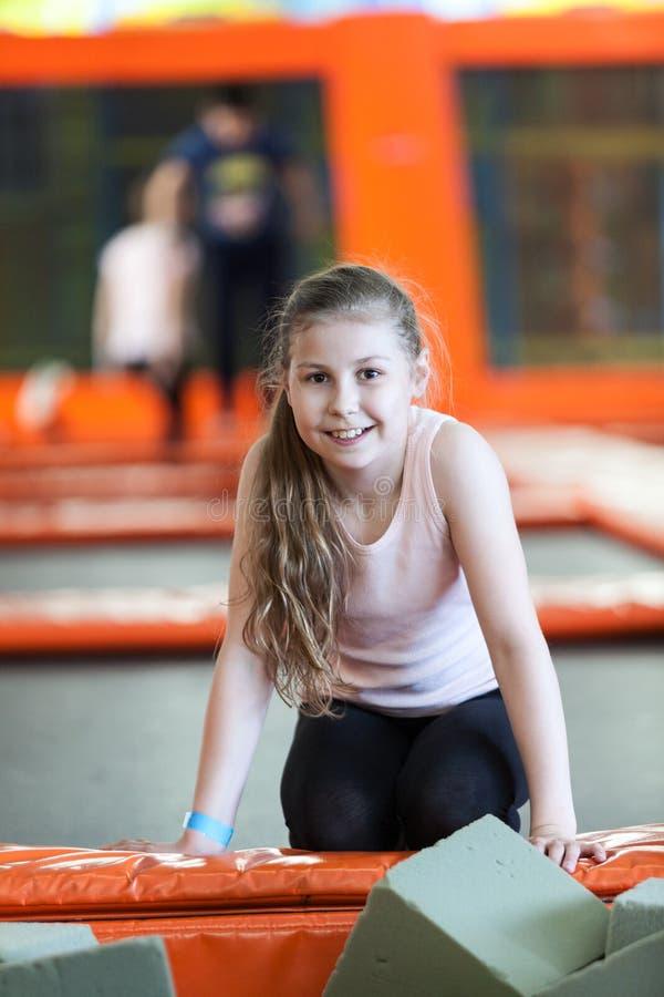 Szczęśliwa i uśmiechnięta dziewczyna odpoczywa podczas gdy skaczący trampoline zdjęcia stock
