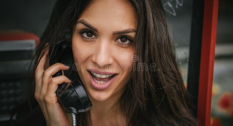 Szczęśliwa i uśmiechnięta kobieta opowiada w retro telefonu budka fotografia stock