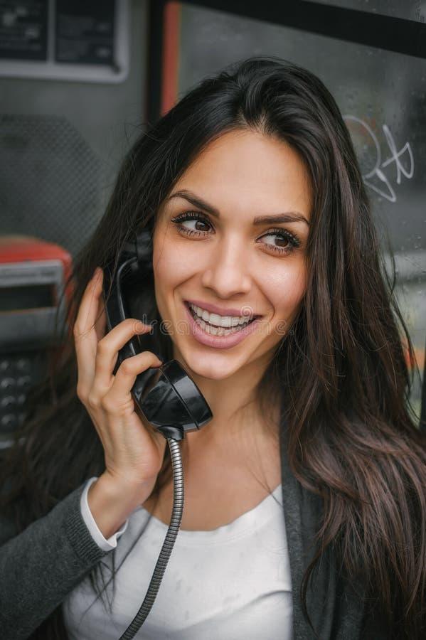 Szczęśliwa i uśmiechnięta kobieta opowiada w retro telefonu budka obraz royalty free