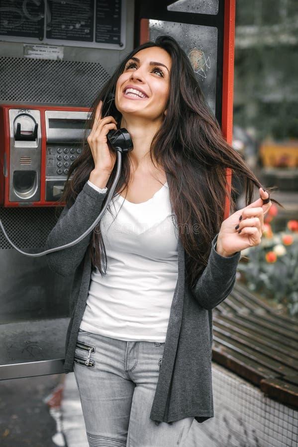 Szczęśliwa i uśmiechnięta kobieta opowiada w retro telefonu budka zdjęcia royalty free