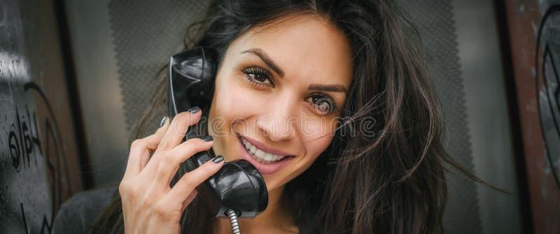 Szczęśliwa i uśmiechnięta kobieta opowiada w retro telefonu budka obrazy royalty free