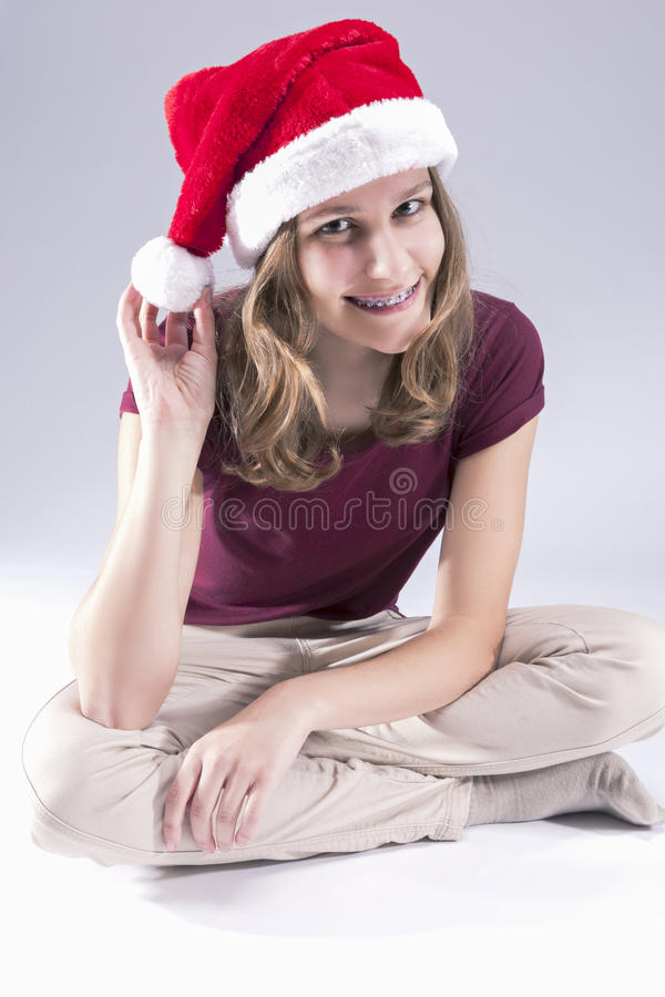 Szczęśliwa i uśmiechnięta nastoletnia dziewczyna Jest ubranym Stomatologicznych zębów wsporniki w Santa kapeluszu obraz stock