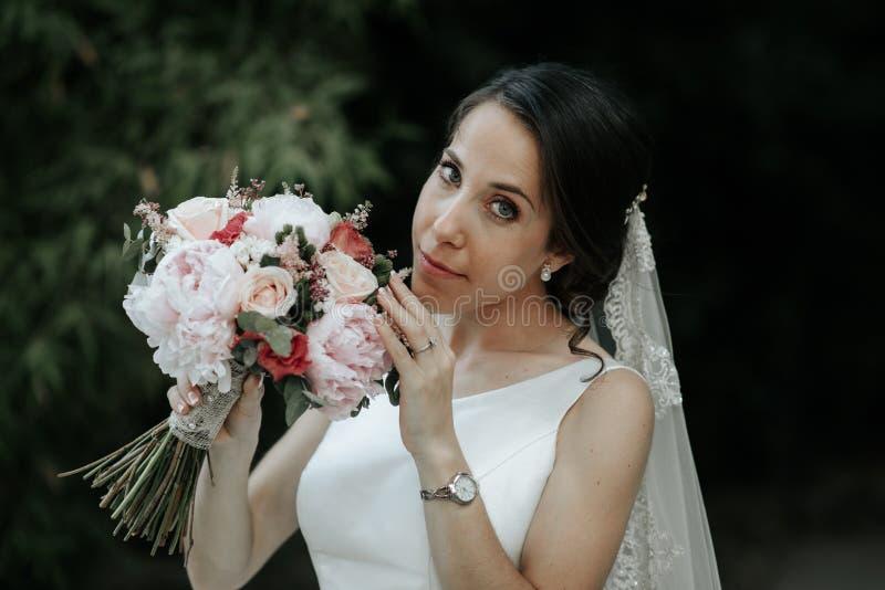 Szczęśliwa i uśmiechnięta panna młoda w luksus sukni z ślubnym bukietem zdjęcia royalty free