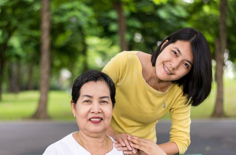 Szczęśliwa i uśmiechnięta starsza azjata matka z córką przy parkiem, Bierze opieki poparcia pojęcie zdjęcia stock