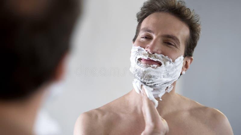 Szczęśliwa i ufna męska kładzenia golenia śmietanka na jego twarzy przed golić fotografia royalty free