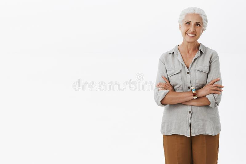 Szczęśliwa i zadowolona europejska babcia w przypadkowym stroju mieniu wręcza krzyżuje i uśmiecha się joyfully ono wpatruje się p zdjęcia stock