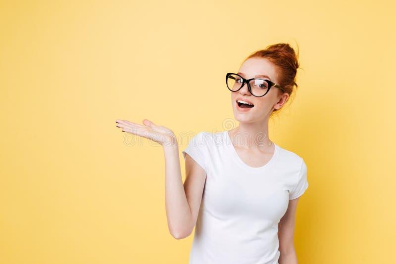 Szczęśliwa imbirowa kobieta trzyma niewidzialnego copyspace na funcie w eyeglasses obrazy royalty free