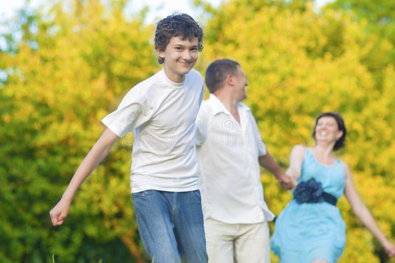 Szczęśliwa Kaukaska rodzina Trzy Ma zabawę i Biega w lato lesie Z Łączyć rękami Wpólnie zdjęcia stock