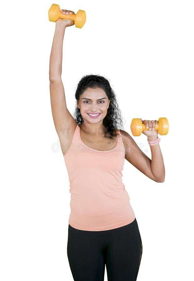 Szczęśliwa kobieta ćwiczy jej bicepsy na studiu obrazy stock
