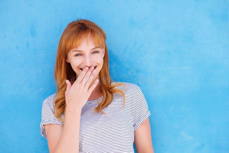 Szczęśliwa kobieta śmia się z ręką usta przeciw błękit ścianie zdjęcie stock