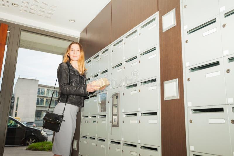 Szczęśliwa kobieta bierze pakunek skrzynkę pocztowa out przy progiem obrazy royalty free