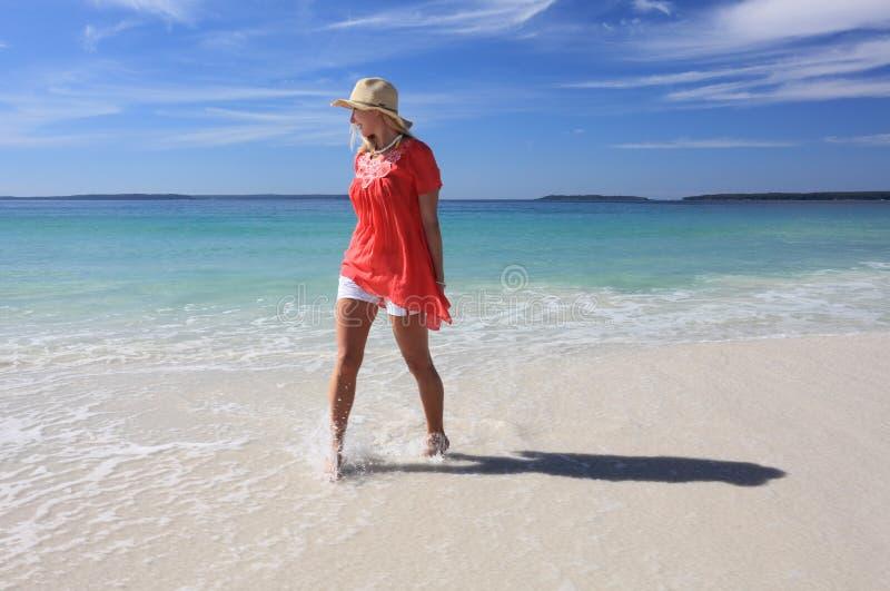 Szczęśliwa kobieta bryzga cieki przy plażą zdjęcia royalty free