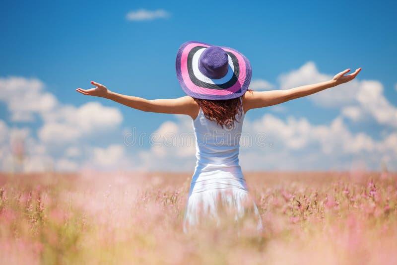 Szczęśliwa kobieta cieszy się życie w polu z kwiatami zdjęcie royalty free