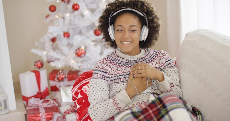 Szczęśliwa kobieta cieszy się jej muzykę przy bożymi narodzeniami zdjęcie royalty free