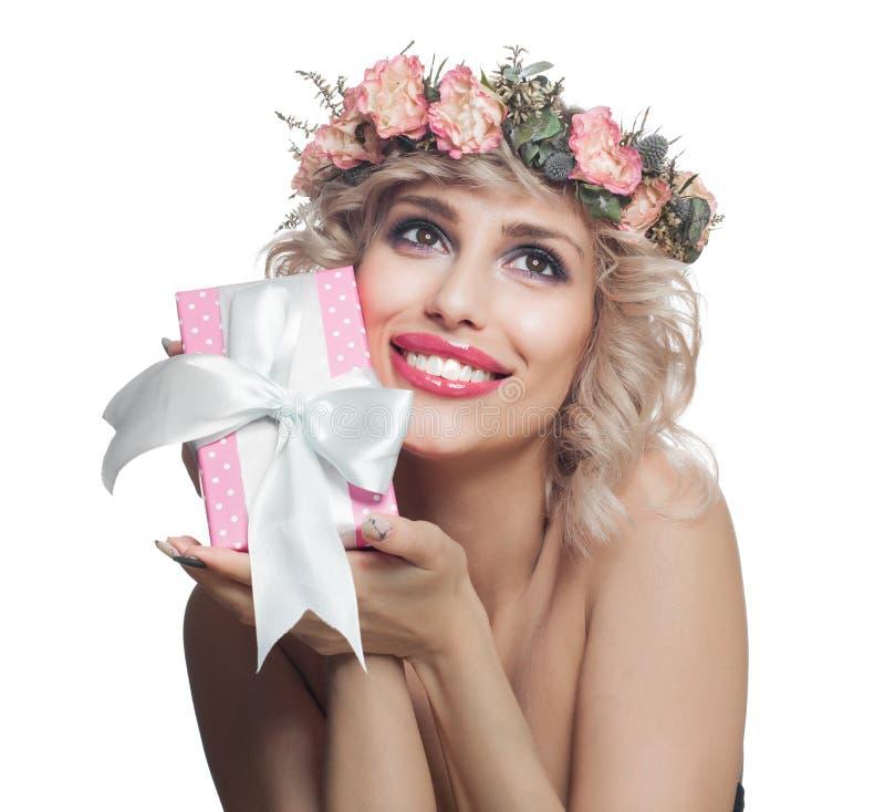 Szczęśliwa kobieta cieszy się prezent i ono uśmiecha się Ładna kobieta z blondynka włosy, makeup i kwiatami odizolowywają zdjęcie royalty free