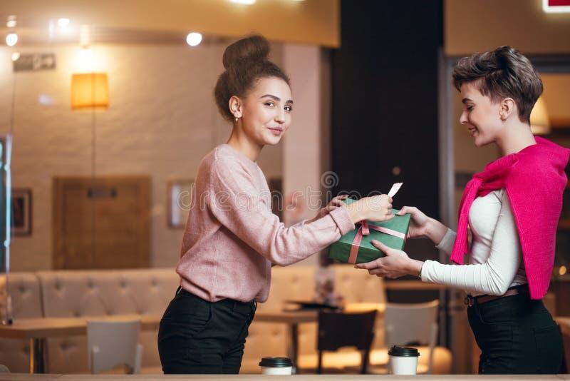 Szczęśliwa kobieta gratuluje jej dziewczyny z teraźniejszości pudełkiem podczas gdy siedzący przy kawiarnią zdjęcie stock