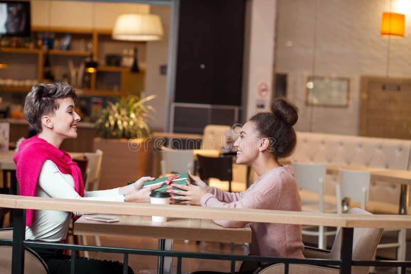 Szczęśliwa kobieta gratuluje jej dziewczyny z teraźniejszości pudełkiem podczas gdy siedzący przy kawiarnią obraz stock