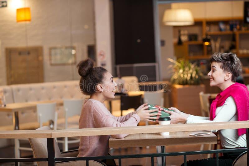 Szczęśliwa kobieta gratuluje jej dziewczyny z teraźniejszości pudełkiem podczas gdy siedzący przy kawiarnią obraz royalty free