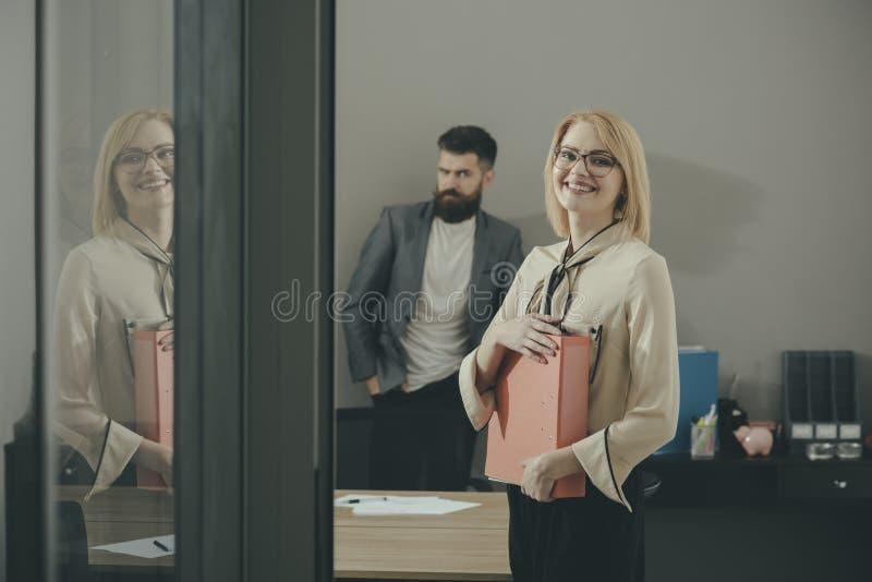 Szczęśliwa kobieta i brodaty mężczyzna w biurowym tle Biznesowej kobiety uśmiech z kartotek falcówkami Papierkowa robota przed tr obraz royalty free