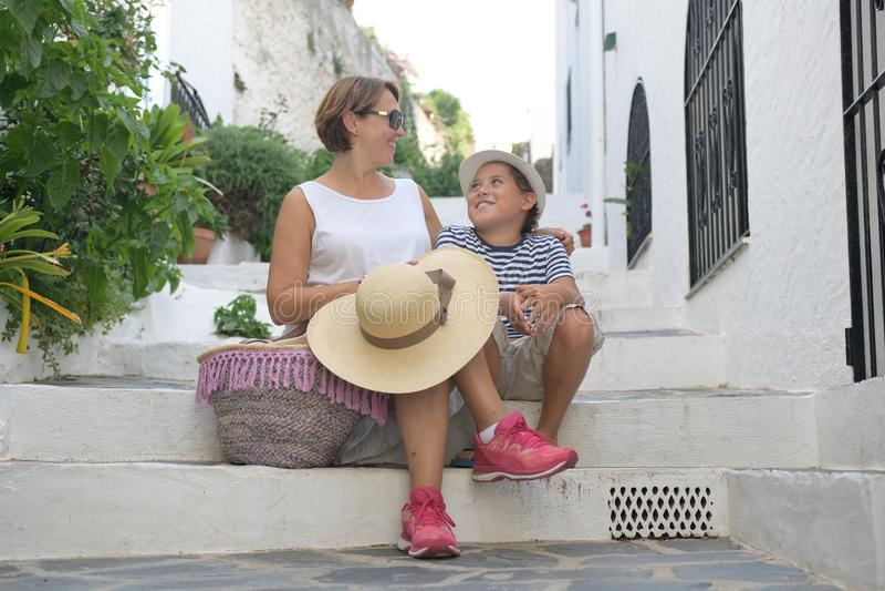 Szczęśliwa kobieta i dzieciak siedzimy na schodkach obrazy stock