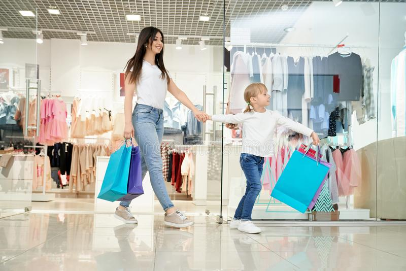 Szczęśliwa kobieta i mała córka wychodzi od sklepu w centrum handlowym obraz royalty free