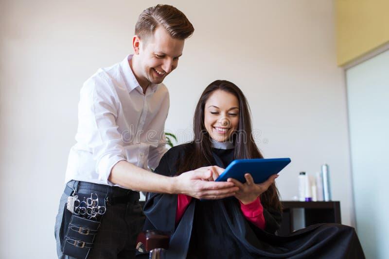 Szczęśliwa kobieta i stylista z pastylka komputerem osobistym przy salonem obrazy stock