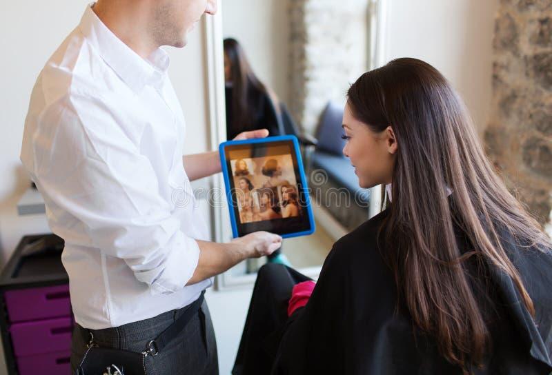 Szczęśliwa kobieta i stylista z pastylka komputerem osobistym przy salonem obrazy royalty free