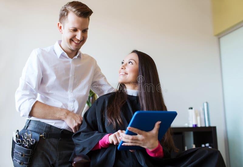 Szczęśliwa kobieta i stylista z pastylka komputerem osobistym przy salonem fotografia stock