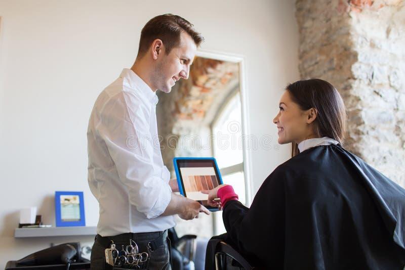 Szczęśliwa kobieta i stylista z pastylka komputerem osobistym przy salonem zdjęcia stock