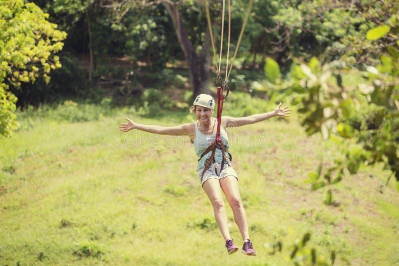 Szczęśliwa kobieta jedzie zamek błyskawiczny linię w luksusowym tropikalnym lesie obraz royalty free