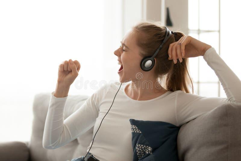Szczęśliwa kobieta jest ubranym słuchawki śpiewacką piosenkę, wyobraża sobie mikrofon w ręce obrazy stock