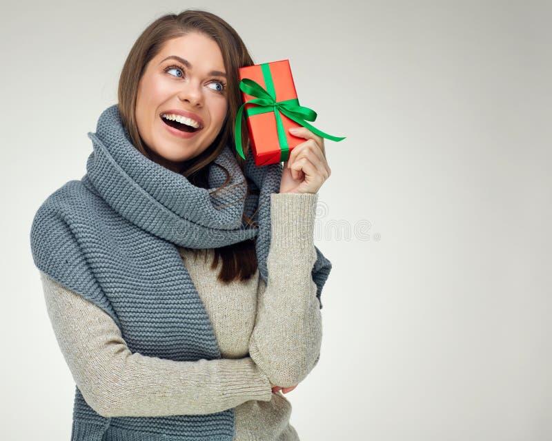 Szczęśliwa kobieta jest ubranym zimy odzieżowego mienia prezenta czerwonego pudełko z gre fotografia stock