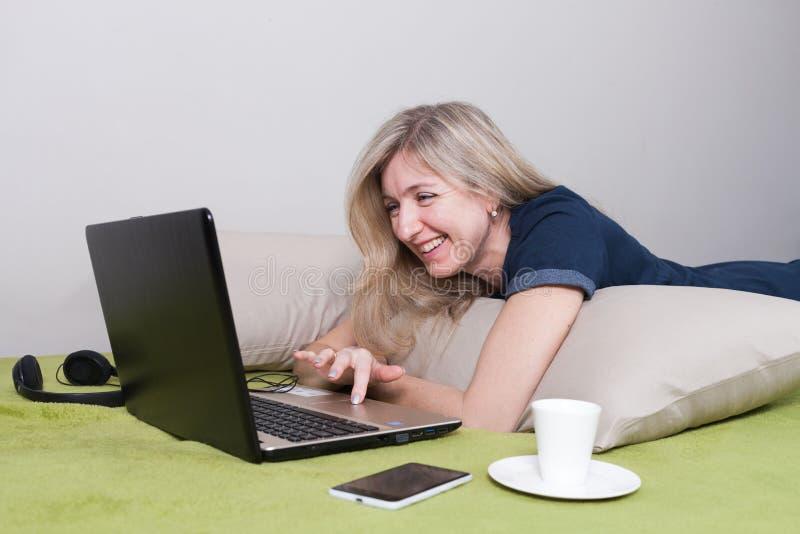Szczęśliwa kobieta kłama na żołądku na poduszkach na zielonej kanapie, spojrzeniach przy laptopem i uśmiechach, obrazy stock
