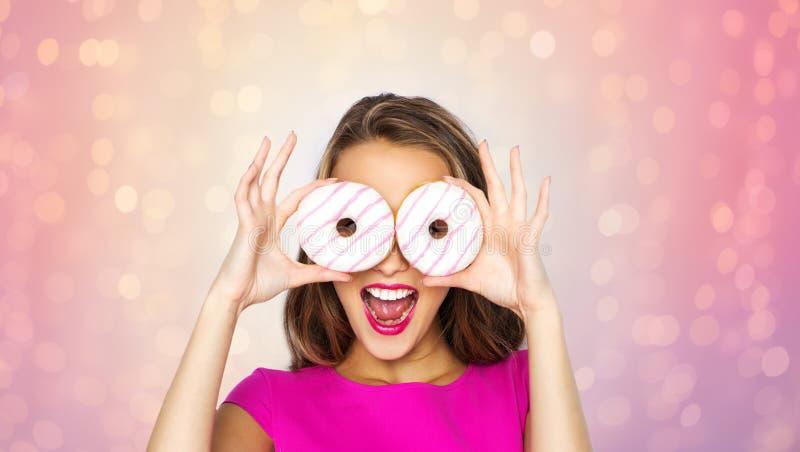 Szczęśliwa kobieta lub nastoletnia dziewczyna patrzeje przez donuts zdjęcia royalty free