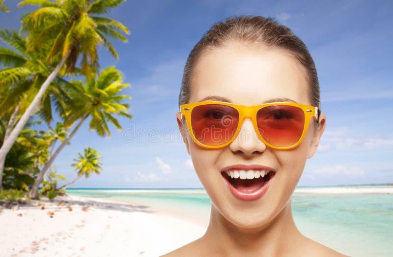 Szczęśliwa kobieta lub nastoletnia dziewczyna w okularach przeciwsłonecznych na plaży zdjęcia royalty free