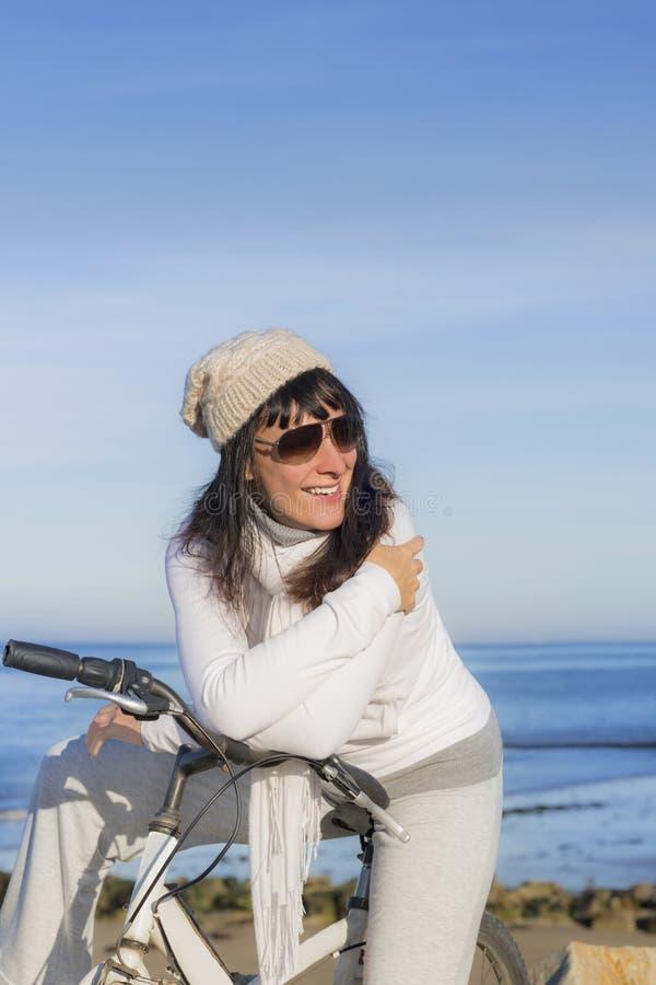 Szczęśliwa kobieta ma przerwę podczas rower przejażdżki wzdłuż morza obrazy stock