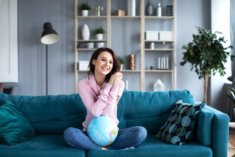 Szczęśliwa kobieta marzy wokoło podróżować wokoło światu, z kulą ziemską w domu fotografia stock
