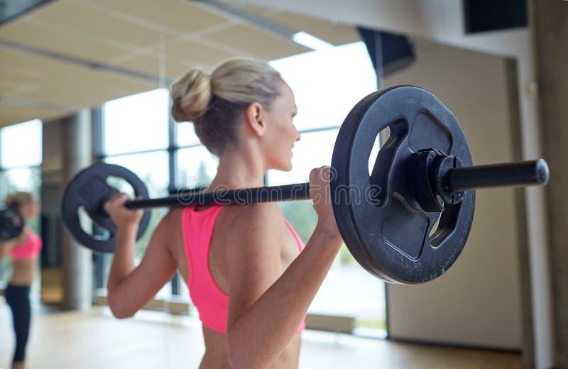 Szczęśliwa kobieta napina mięśnie z barbell w gym fotografia stock