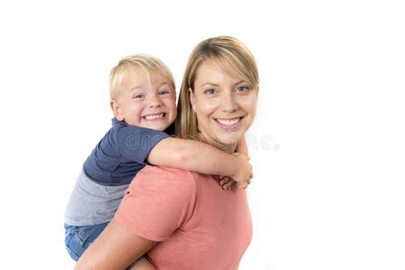 Szczęśliwa kobieta niesie jej uroczej 3 lat chłopiec na jej z powrotem ono uśmiecha się szczęśliwy i rozochocony w wpólnie rodzin obraz royalty free