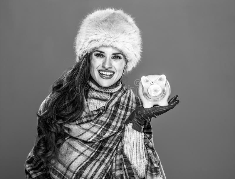 Szczęśliwa kobieta odizolowywająca na zimnym błękitnym tle pokazuje prosiątko banka zdjęcie royalty free