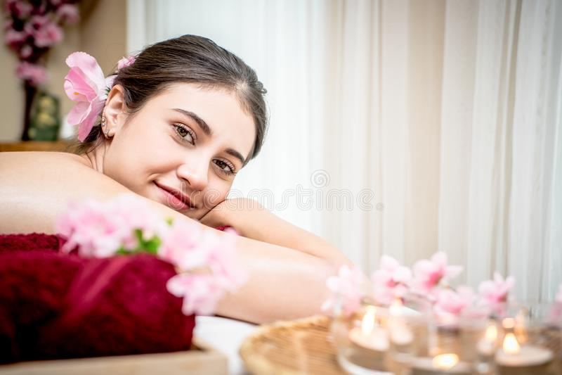 Szczęśliwa kobieta ono uśmiecha się podczas gdy relaksujący na aromata zdroju łóżku zdjęcia stock