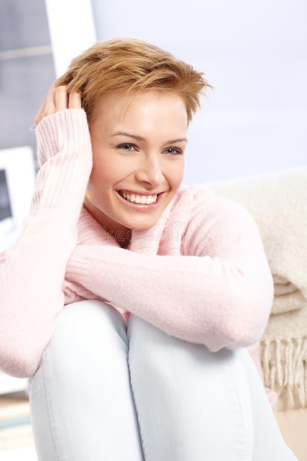 Szczęśliwa kobieta ono uśmiecha się z ciągnący w górę nóg zdjęcia royalty free