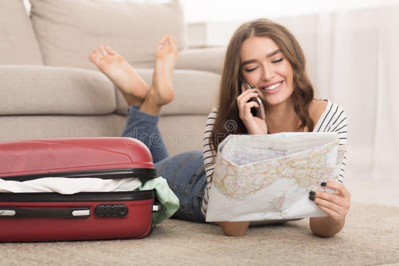 Szczęśliwa kobieta opowiada na telefonie, patrzeje mapę obrazy royalty free