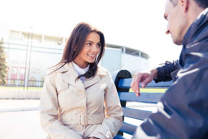 Szczęśliwa kobieta opowiada z mężczyzna outdoors fotografia stock