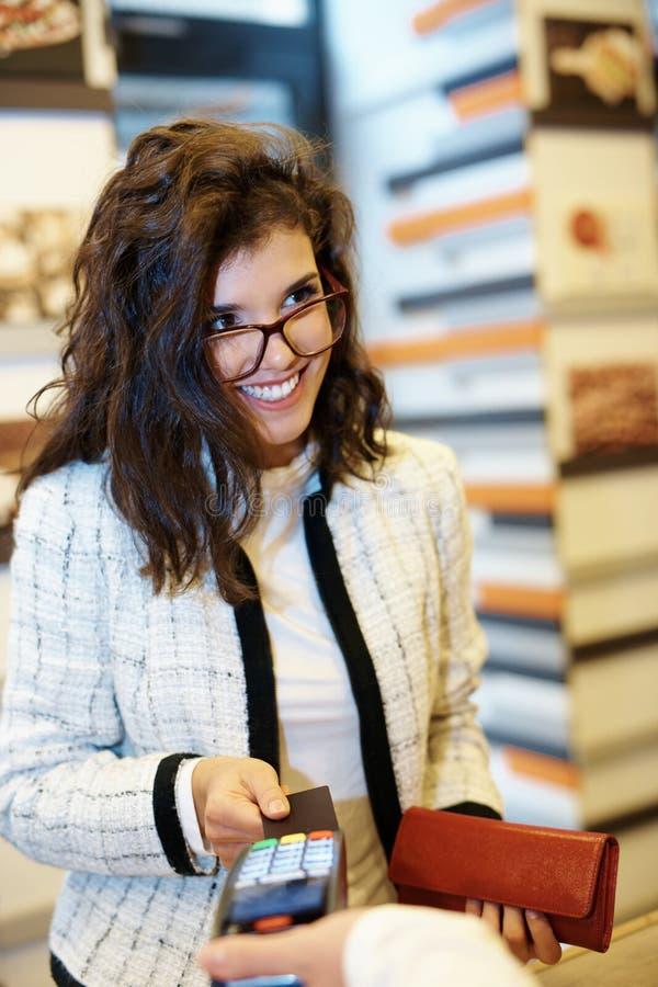 Szczęśliwa kobieta płaci kredytową kartą zdjęcia stock