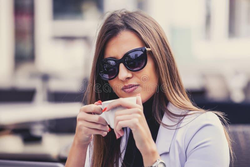Szczęśliwa kobieta pije kawę w ulicznej kawiarni obraz stock
