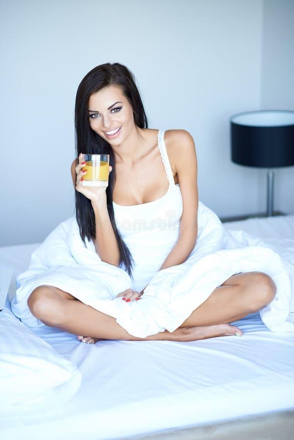 Szczęśliwa kobieta pije sok pomarańczowego w łóżku fotografia stock