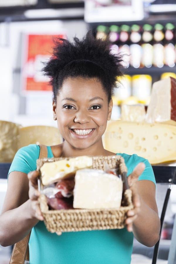 Szczęśliwa kobieta Pokazuje Serowego kosz W sklepie spożywczym obrazy stock