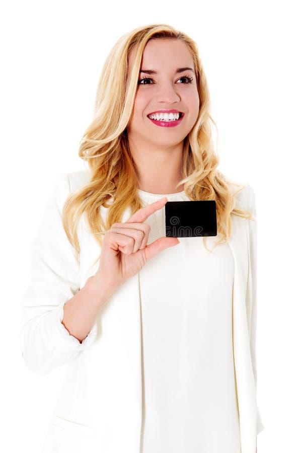 Szczęśliwa kobieta pokazuje wizytówkę, odizolowywającą nad białym backround obraz stock