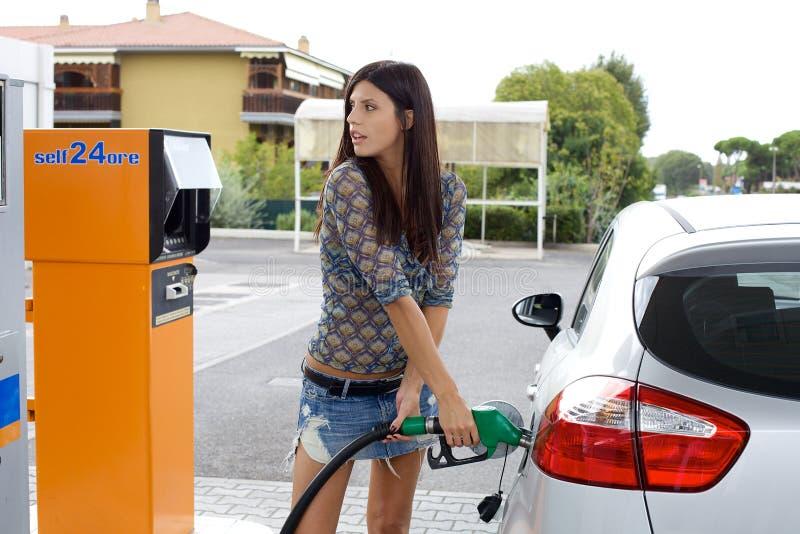 Szczęśliwa kobieta pompuje gaz w samochodzie zdjęcia royalty free